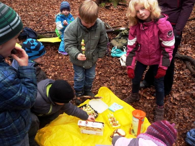 Kinder naschen von einer Picknickdecke.