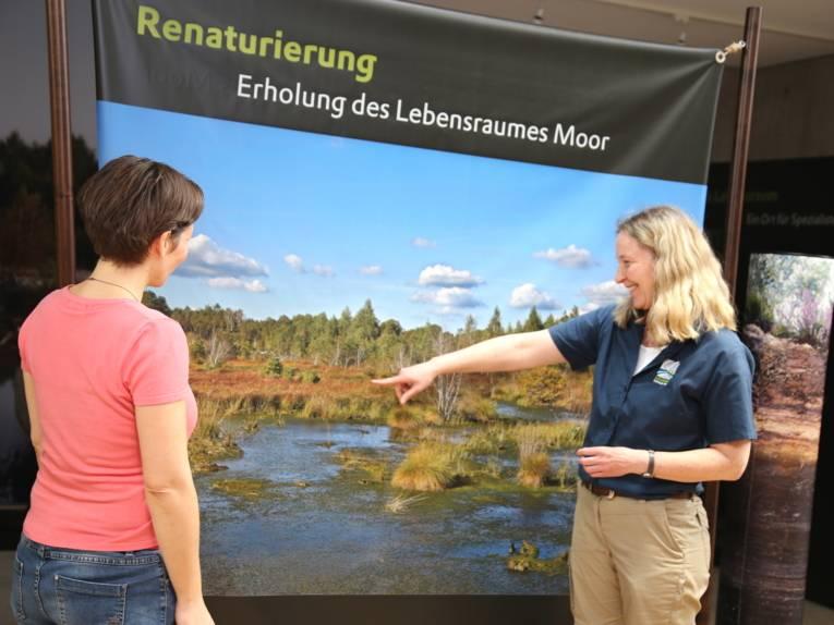 Zwei Frauen betrachten das Bild einer Moorlandschaft.