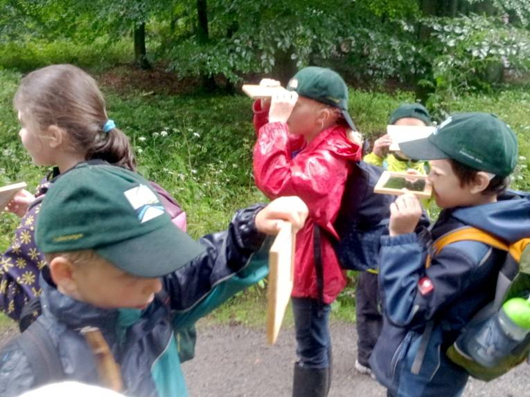 Drei Jungen und zwei Mädchen halten jeweils einem kleinen Spiegel in den Händen und betrachten darüber Dinge hinter, über oder unter sich.