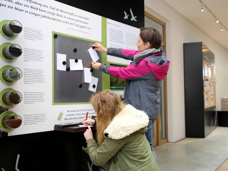 Zwei Frauen schreiben Kärtchen und hängen sie an eine Magnettafel. In Schaugläsern sind fünf Naturmaterialien zu sehen, zum Beispiel Torfmosse, Holzfasern und Rindenhumus.