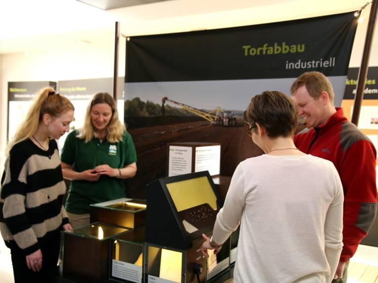 """Drei Besucherinnen und ein Besucher entdecken die Themeninsel """"Torabbau industriell""""."""