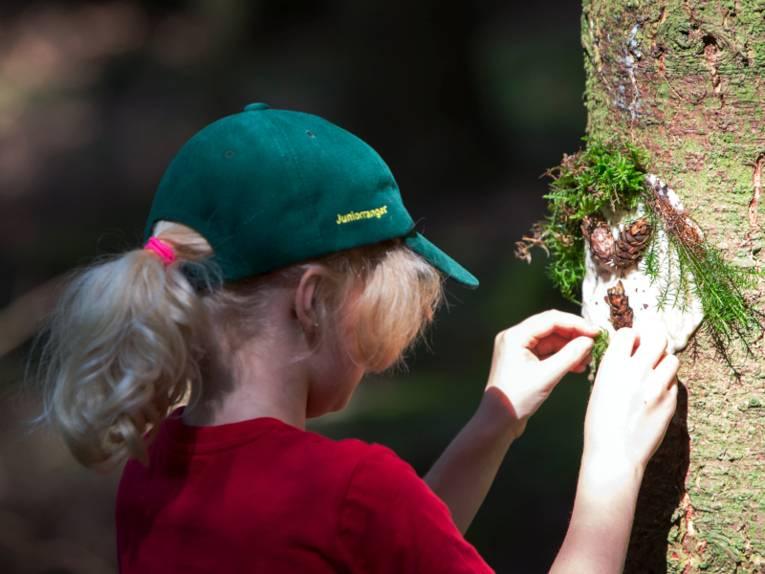 Ein Mädchen modelliert aus Moos und Tannenzapfen ein Gesicht auf einen Baumstamm.