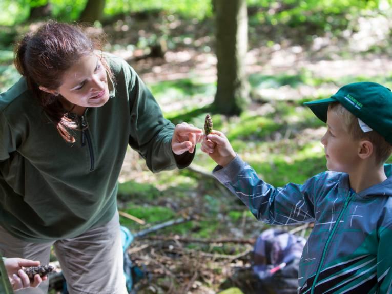 Ein Junge hält einen Tannenzapfen in den Händen, eine Frau zeigt mit einem Finger darauf.