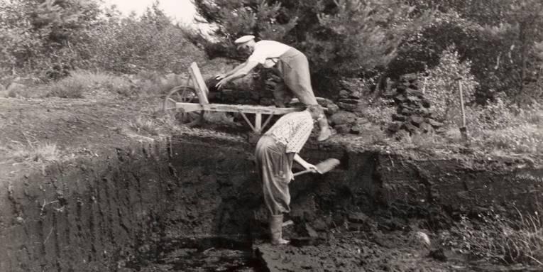 Zwei Männer arbeiten im Torfabbau: Einer steht im Morast und sticht Torf, der andere steht auf dem noch nicht abgestochenen Torfboden und belädt einen Holzkarren mit getrockneten Torfsoden.