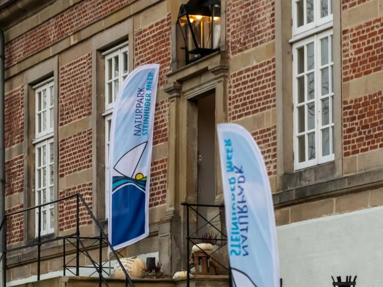 Zwei Beachflags mit dem Logo des Naturparks Steinhuder stehen auf einer Treppe zu einem Eingang von Schloss Landestrost in Neustadt am Rübenberge.