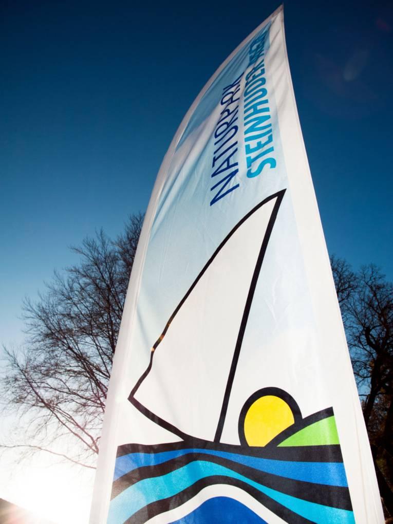 Freistehende Fahne mit dem Logo des Naturparks Steinhuder Meer