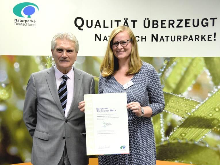 """Ein Mann und eine Frau stehen nebeneinander, die Frau hält ein Zertifikat in ihren Händen. Im Hintergrund zeigt ein Banner die Blätter einer Grünpflanze, darüber steht der Text """"Qualität überzeugt. Natürlich Naturparke!"""""""
