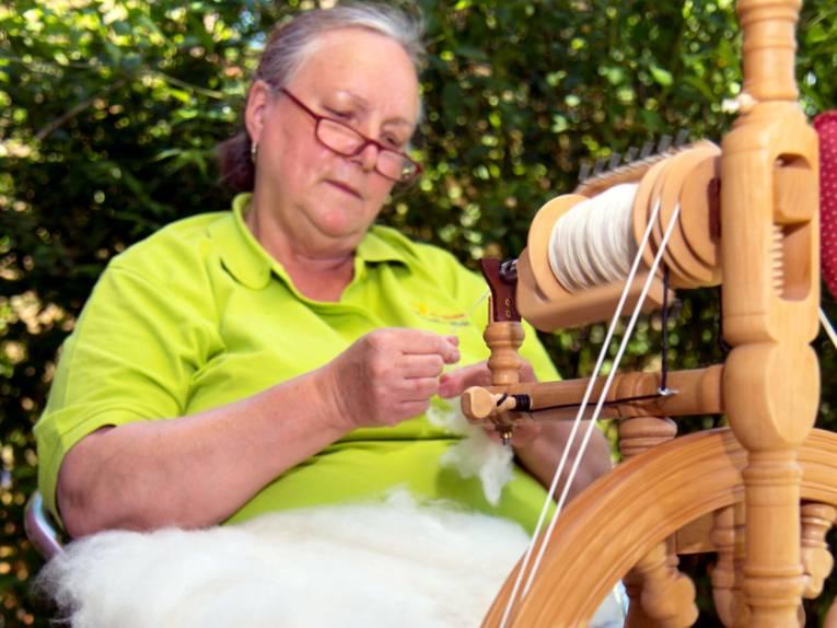 Eine Frau sitzt an einem Spinnrad und spinnt grobe Wolle zu einem gleichmäßigen Faden.