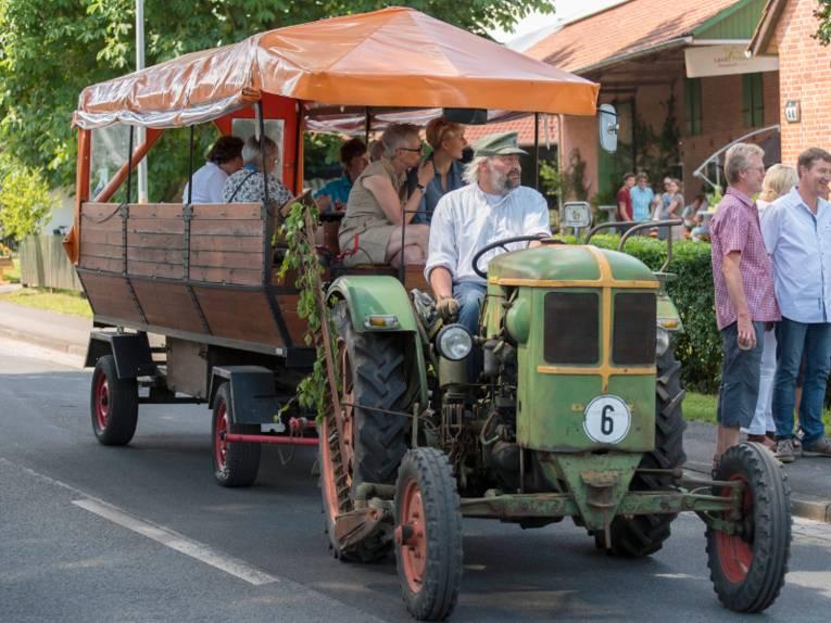 Ein Oldtimer-Trecker zieht einen Planwagen, darauf fahren Menschen mit.
