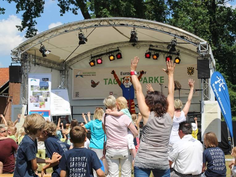 Menschen tanzen vor einer Bühne, darauf tanzt ein Maskottchen im Tigerkostüm.