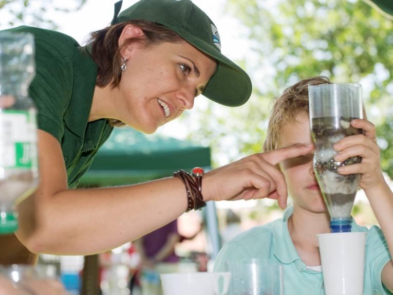 Eine Frau und ein Junge experimentieren mit einer Wasserflasche und einem Trinkbecher aus Plastik.