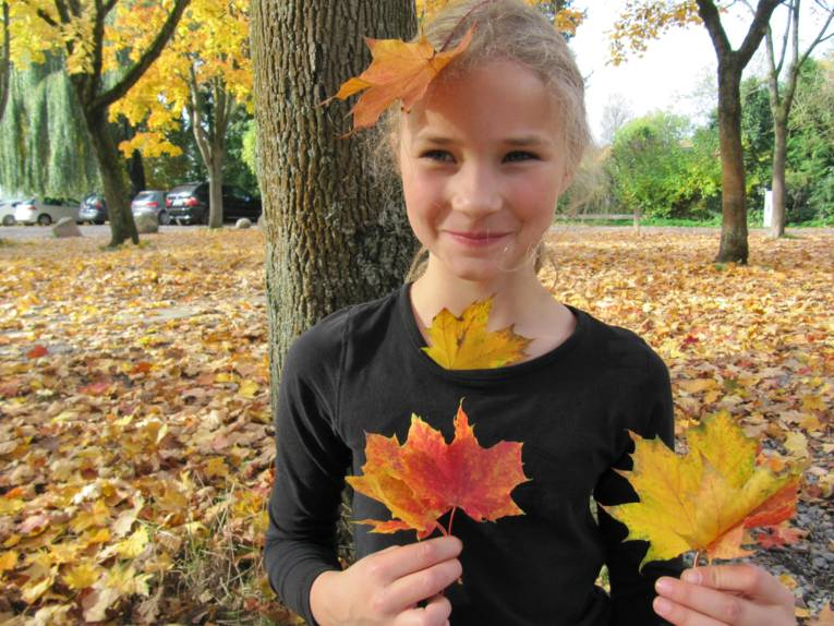 Ein Mädchen steht unter einem Baum. Herbstlaub liegt auf dem Fußboden, auch auf dem Kopf des Mädchens liegt ein Blatt und es hält Blätter in den Händen.