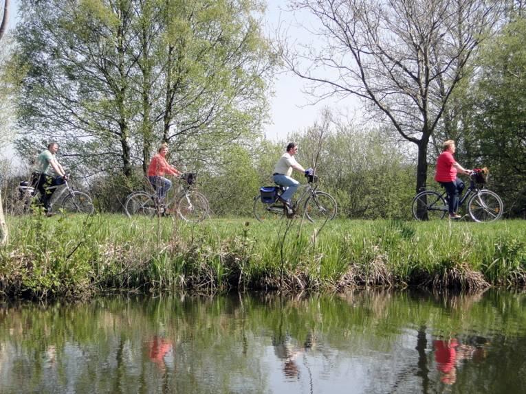 Radfahrende in grüner Landschaft, parallel zu einem Gewässer.