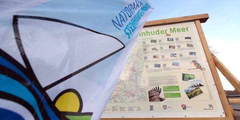 Eine Strandfahne mit Naturparklogo steht vor einer Naturpark-Infotafel.