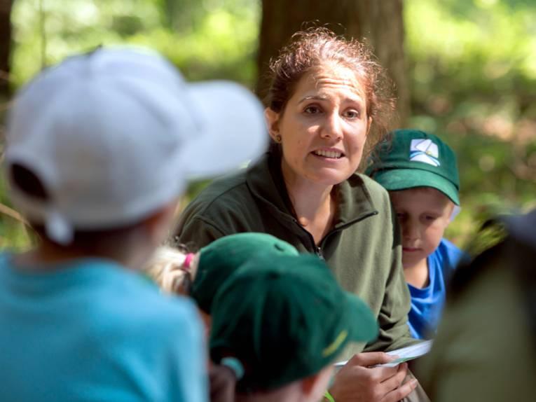 Eine Frau wird von Kindern umringt, die ihr gespannt lauschen.