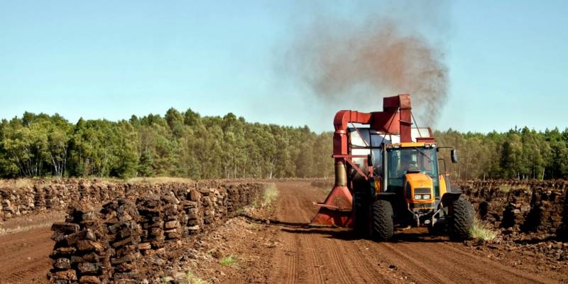 Ein Traktor fährt über eine Torffläche