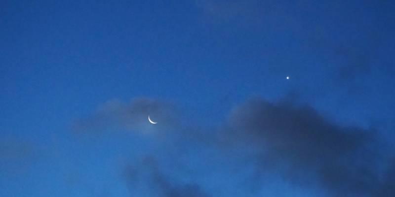 Abendhimmel mit Mond, einem Stern und dunklen Wolken.