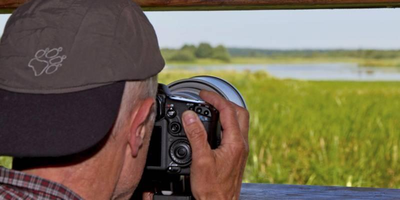 Ein Mann ist an einem Aussichtspunkt und schaut durch den Sucher seiner Kamera auf ein Feuchtgebiet.