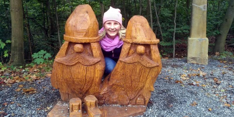 Ein Kind steht zwischen zwei aus Holz geschnitzten Wichtelmännchen.