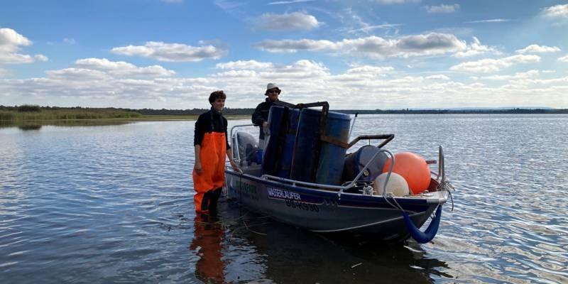 Ein Mann trägt eine orangefarbene Wathose und steht neben einem Boot. In dem Boot ist ein zweiter Mann und jede Menge Unrat einer Müllsammelaktion.