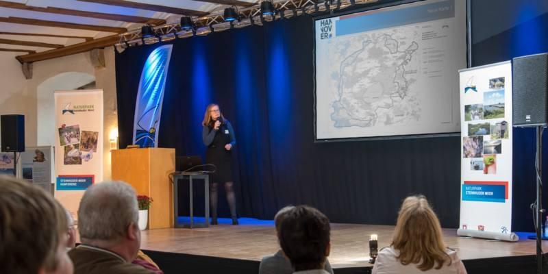 Blick auf eine Bühne, dort steht eine Frau an einem Rednerpult.