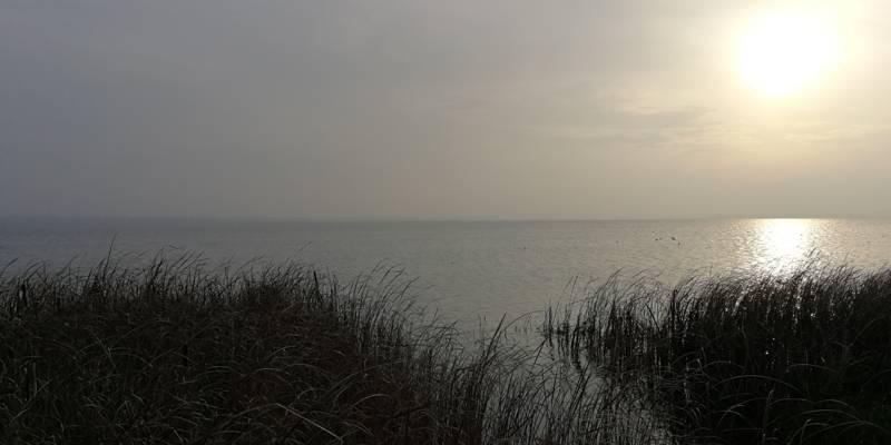 Die Sonne scheint am Steinhuder Meer durch einen bedeckten Himmel.