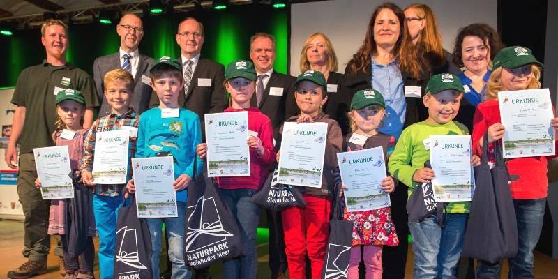 Acht Kinder und acht Erwachsene stehen auf einer Bühne, die Kinder stehen in der vorderen Reihe und halten Urkunden in ihren Händen.