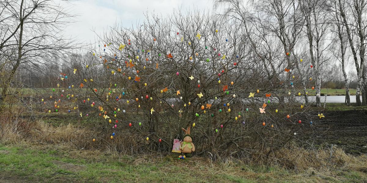 Bunte Eier und Schmetterlinge zieren einen Strauch. Am Stamm des Strauchs lehnt eine Osterhasenfigur.