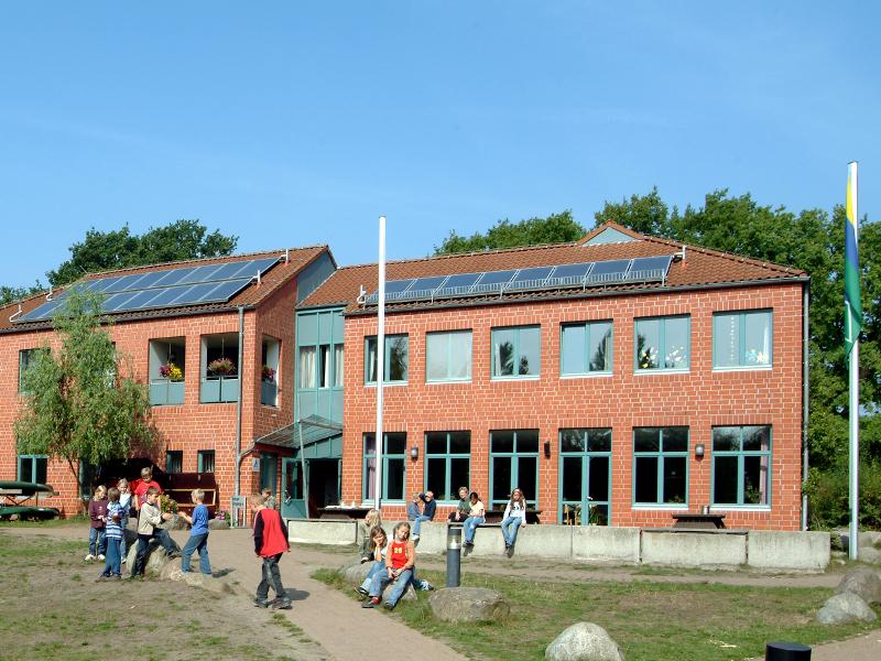 Kinder spielen vor einem Zweigeschossigen Gebäude aus roten Backsteinen.